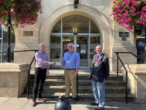 Representative from Chippenham Hospital Radio olleting their community donation cheque with Councillor Nick Murry and Mayor of Chippenham COuncillor John Scragg. The image is taken outside the front of the Town Hall.