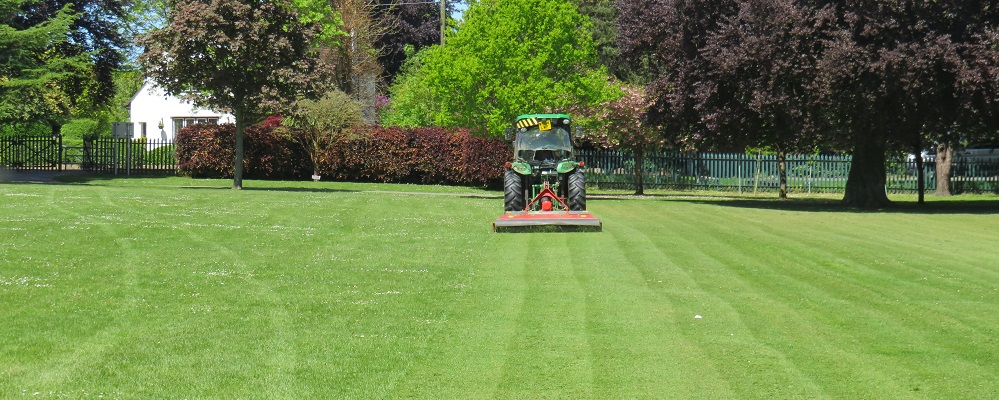 Tractor in John Coles Park cutting the grass in the summer